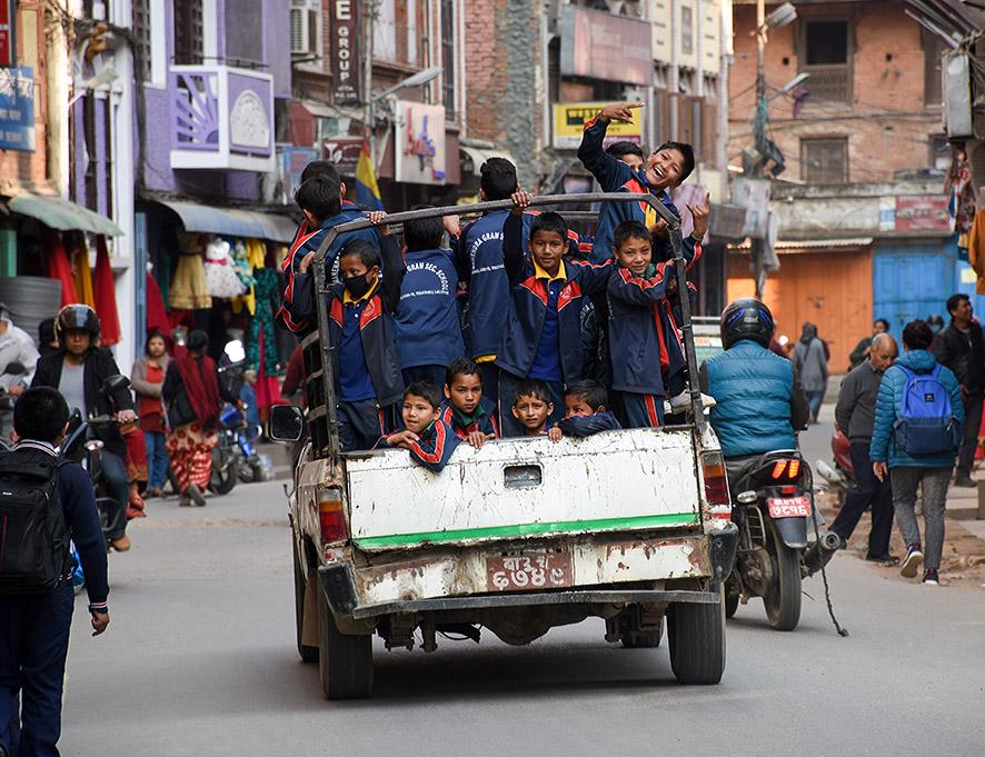 Nepalese kinderen in een truck rijden door de straten van Kathmandu