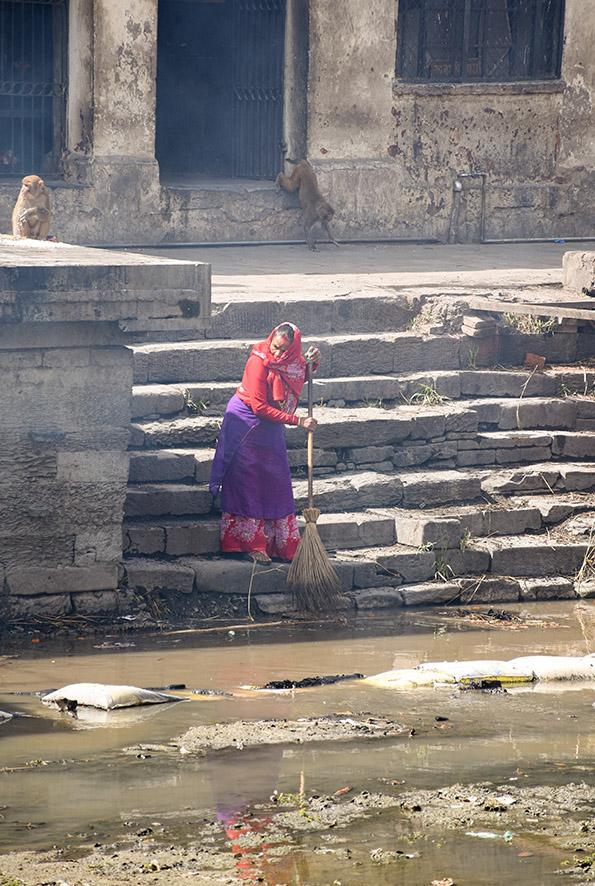 Vrowu veegt de trappen van de Pashupatinath tempel