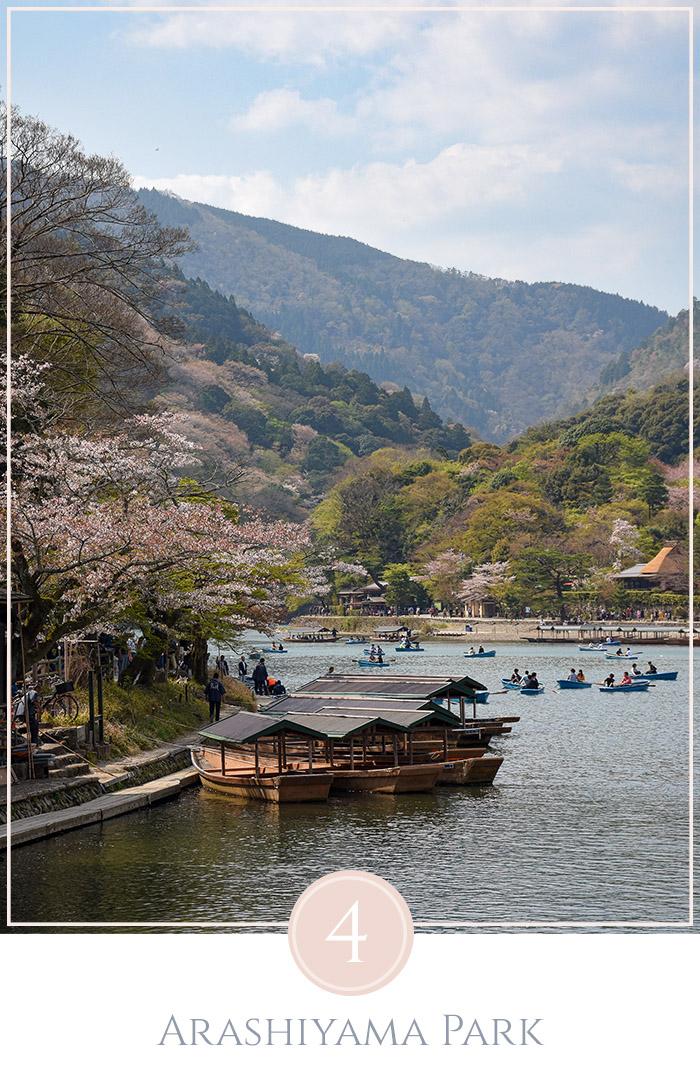 Boten op de rivier bij Arashiyama park Kyoto, n de omringende heuvels staan cherry blossoms