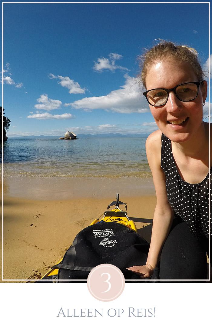 Zittend op het strand bij een kayak in Abel Tasman National Park Nieuw-Zeeland, met de split apple rock in de zee op de achtergond